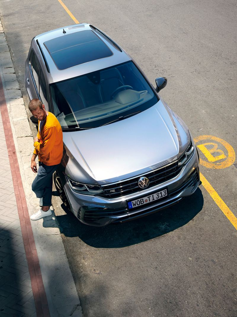"""Man leans against the front of a VW Tiguan R-Line """"Black Style"""""""