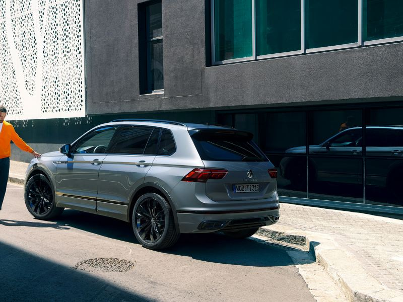 """Man strokes the front of a VW Tiguan R-Line """"Black Style"""" with his fingertips"""