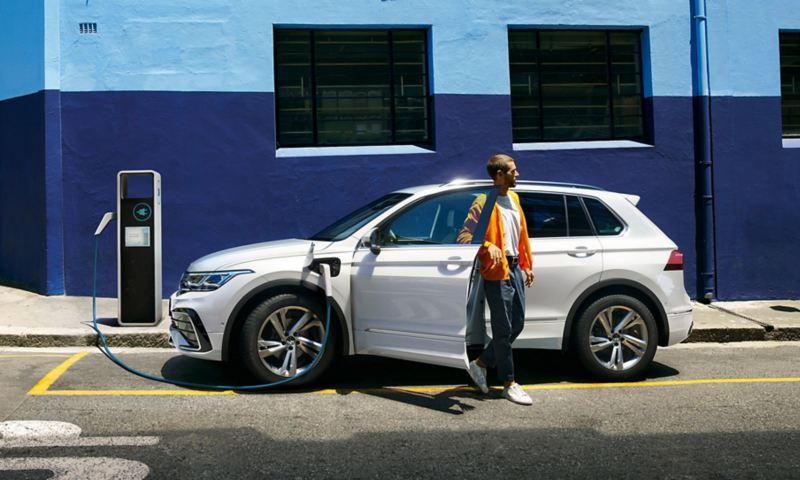 uomo aspetta vicino alla sua Volkswagen Tiguan eHYBRID in ricarica