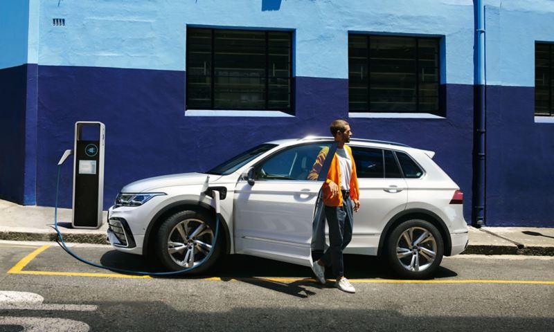 Volkswagen Tiguan hybride rechargeable en blanc, vue latérale, en charge au bord de la route, une personne descend