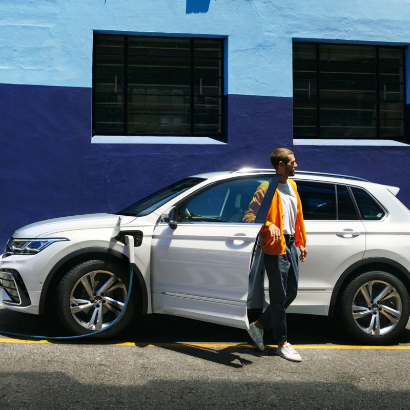 The new Tiguan eHybrid  Side view of the VW Tiguan eHybrid in white, which charges at the roadside. Young man gets out of the driver's side.