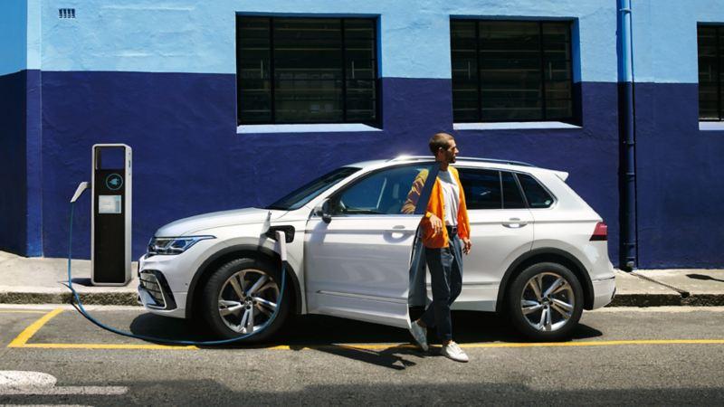 Volkswagen Tiguan eHybrid står på laddning, en man kliver ur