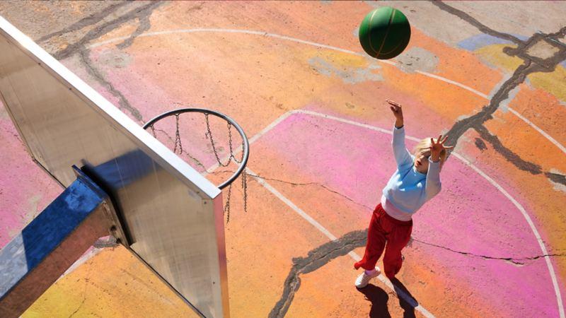 Une femme en milieu urbain lance un ballon de basket vers un panier. Mode de vie.