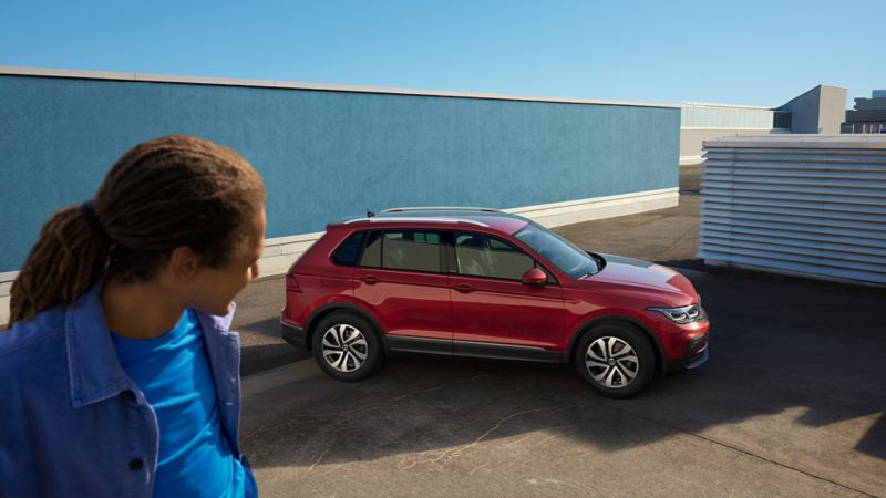 Red VW Tiguan stands in an urban environment in front of a blue wall. There is a man on the left-hand side of the picture.