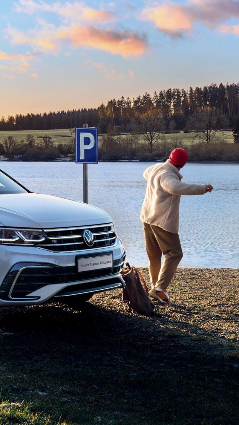 """Vista 3/4 frontale di Volkswagen Nuova Tiguan Allspace in versione """"R-Line"""" parcheggiata accanto a un lago."""