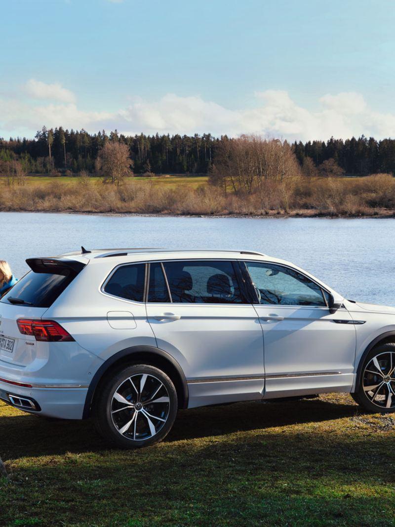 """Vista laterale di Volkswagen Nuova Tiguan Allspace in versione """"R-Line"""" parcheggiata vicino a un lago."""