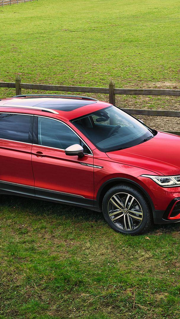Un Tiguan Allspace Elegance rouge avec des vitres arrière teintées est garé en dehors de la route près d'un paddock.