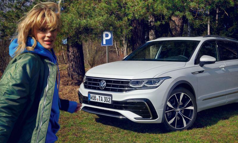 """Una ragazza si avvicina a una Volkswagen Nuova Tiguan Allspace in versione """"R-Line"""", vista frontalmente, parcheggiata in un prato."""