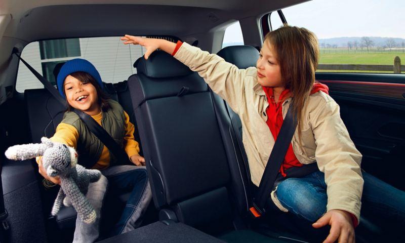 """Due bambini giocano seduti sulla seconda e terza fila dei sedili posteriori di Volkswagen Nuova Tiguan Allspace in versione """"Elegance""""."""