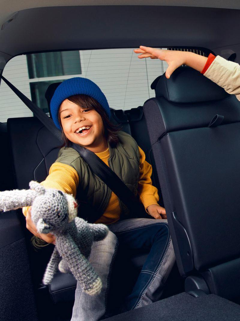 Zwei Kinder sitzen im Innenraum eines Tiguan Allspace Elegance: Ein Mädchen in der zweiten Sitzreihe, ein Junge in der dritten Sitzreihe.