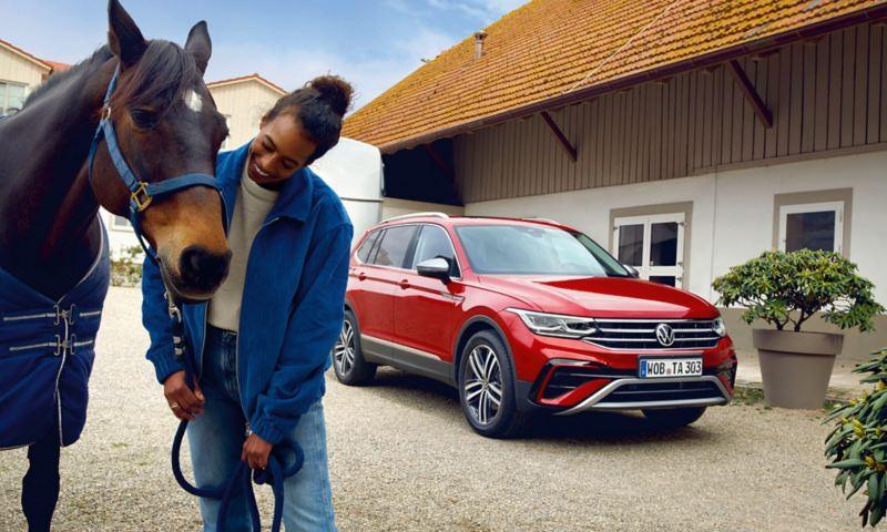 Un Tiguan Allspace Elegance rouge avec une remorque à cheval est garée dans une ferme équestre. Une femme avec un cheval brun se tient devant elle.