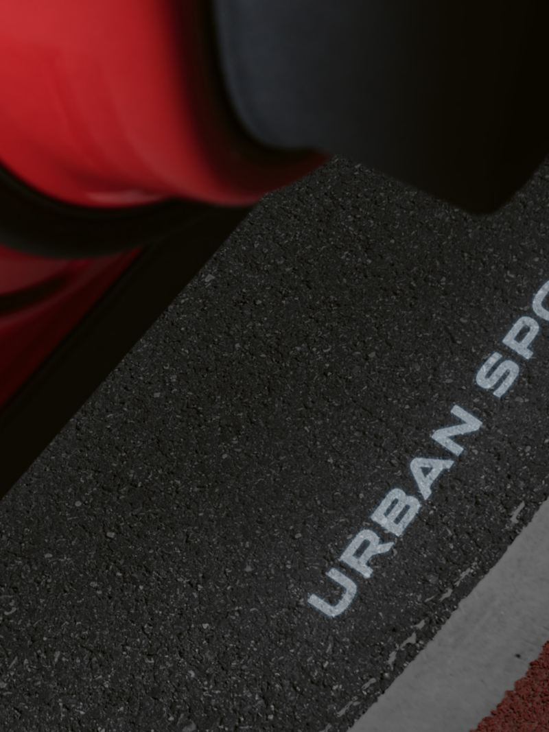 """Logo projection of the lettering """"URBAN SPORT"""" on the floor from the open driver's door of the Tiguan URBAN SPORT."""