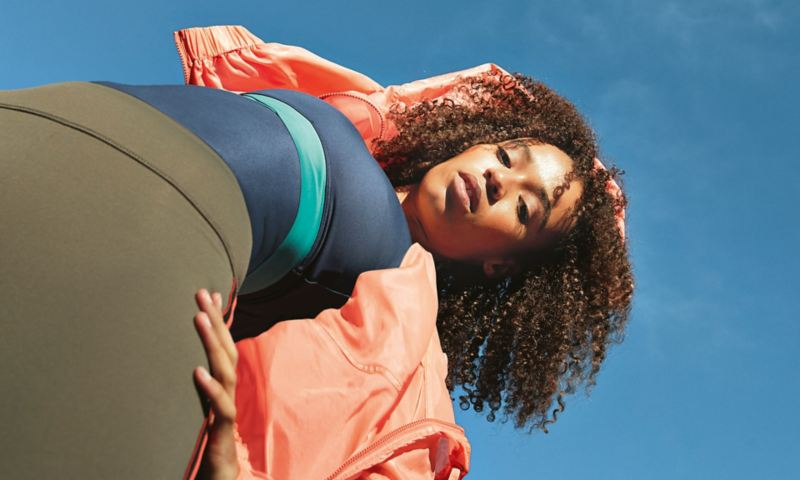 View from below of a young woman in sportswear looking into the camera.