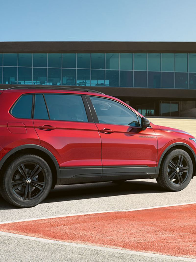 A red Tiguan URBAN SPORT stands on a runway in front of futuristic building and blue sky, view of the side and rear.