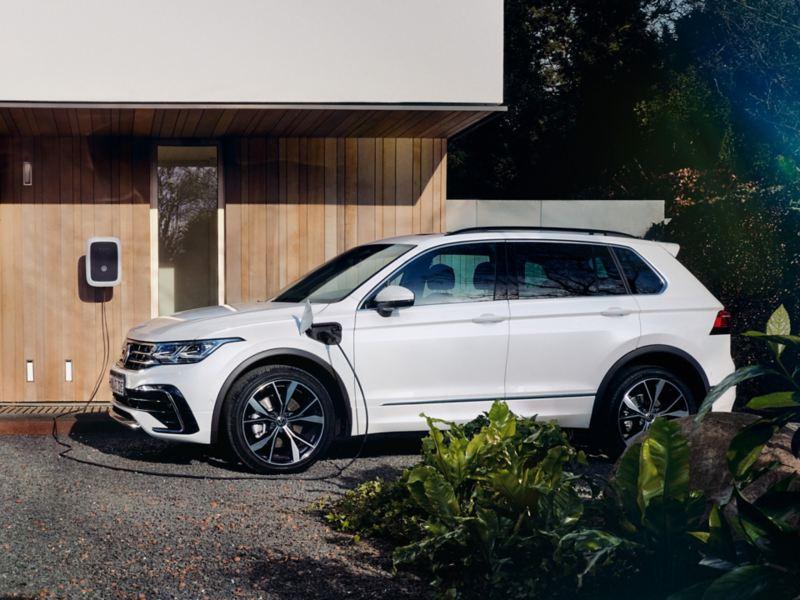 Vista laterale di Volkswagen Tiguan eHYBRID, parcheggiata fuori da un edificio e in carica presso una wallbox.