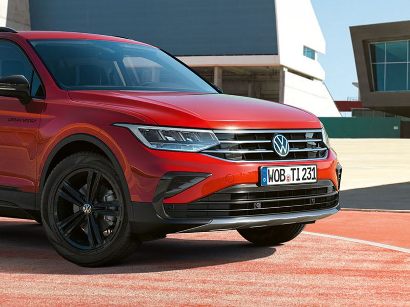 View of the front of a red Tiguan URBAN SPORT with black exterior mirrors and LED lights.