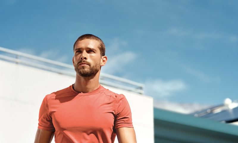 View on a young man in red sports t-shirt in front of a white building and blue sky.