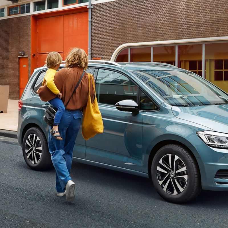 Woman carrying a child next to a blue VW