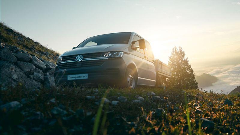 Vista 3/4 frontale dal basso del furgone Transporter Volkswagen parcheggiato in montagna.