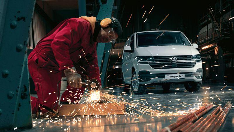 En hvit Volkswagen Transporter varebil står parkert i en hall. I forgrunn ser man en sveiser ikledd rød kjeledress som skjærer i stål som gnistrer