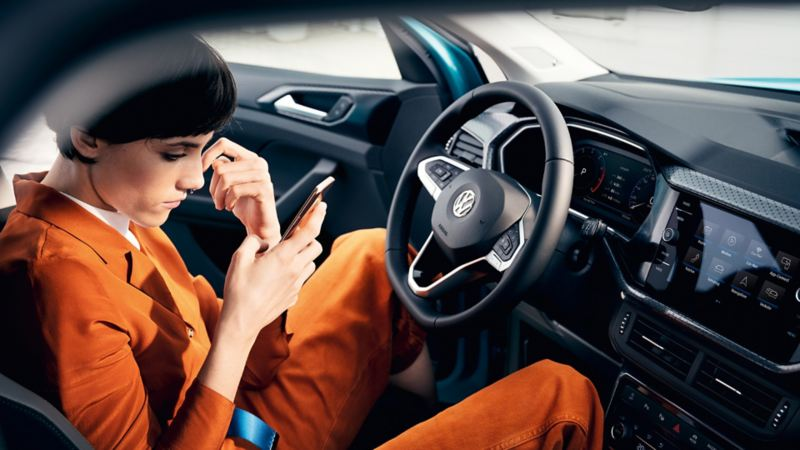 Woman sitting in a car and looking at her phone