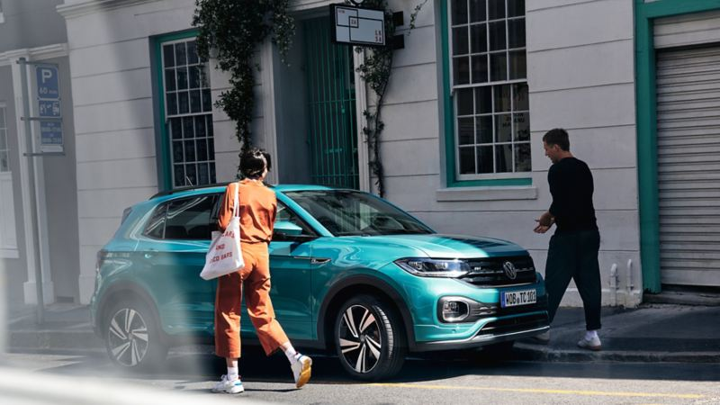 T-Cross Volkswagen parcheggiata in strada con uomo e donna che camminano per salire a bordo