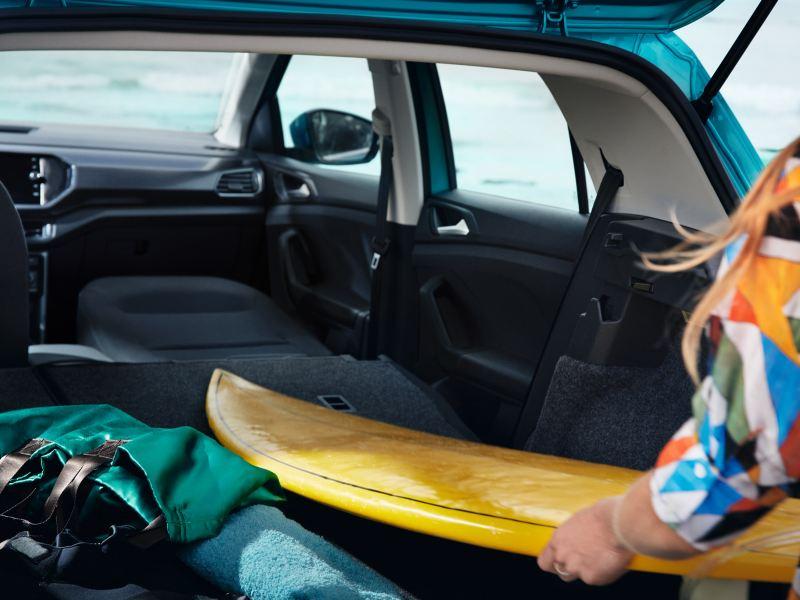 Μια γυναίκα με πορτοκαλί μπλούζα φορτώνει τη σανίδα του σερφ στο Volkswagen T-Cross, για την οποία αναδιπλώθηκε το κάθισμα του συνοδηγού