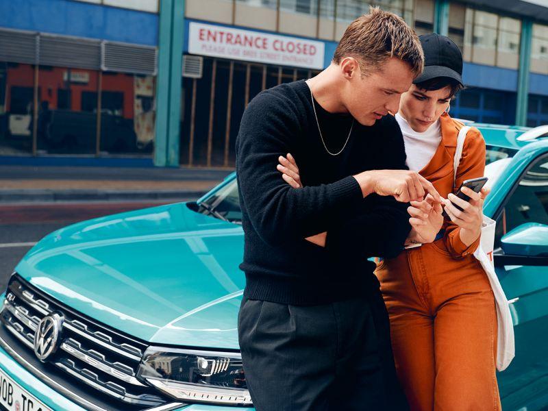 Ein Mann und eine Frau lehnen am Auto