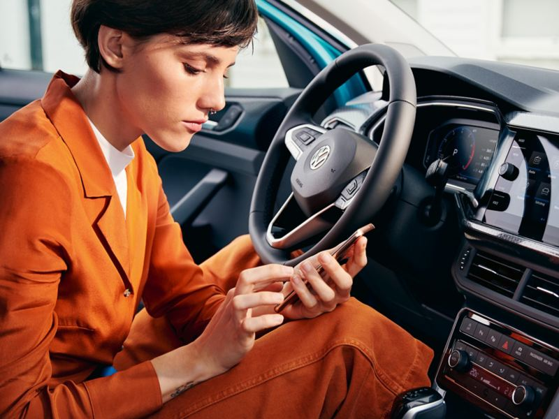 A woman holding a mobile phone in a VW vehicle