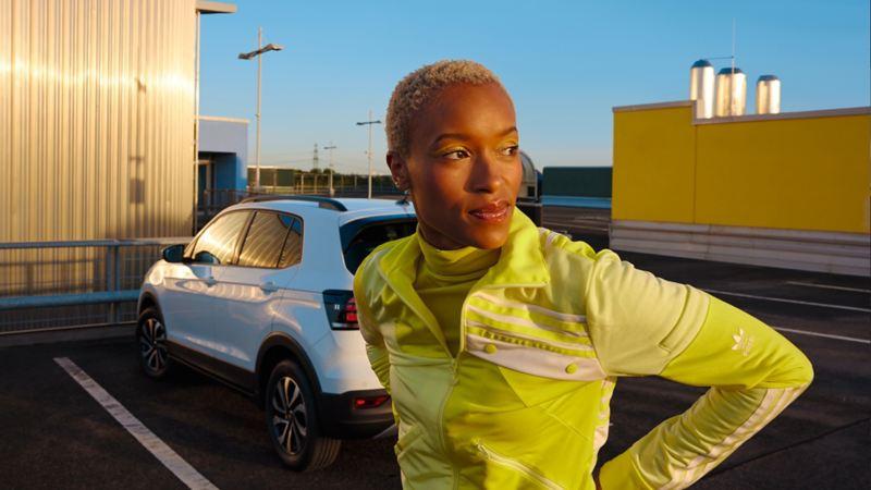 Une VW T-Cross ACTIVE blanche sur un parking urbain. Une femme portant une chemise jaune se tient devant elle.