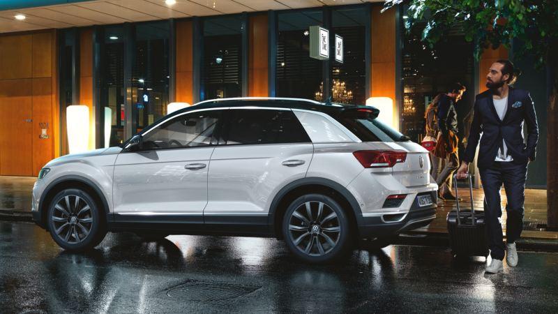 Chico caminando detrás de Volkswagen T-Roc blanco aparcado en la ciudad de noche visto de costado