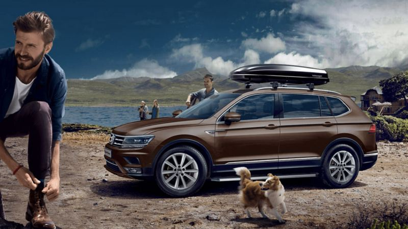 Vista laterale di Volkswagen Tiguan Allspace parcheggiata davanti ad un lago.