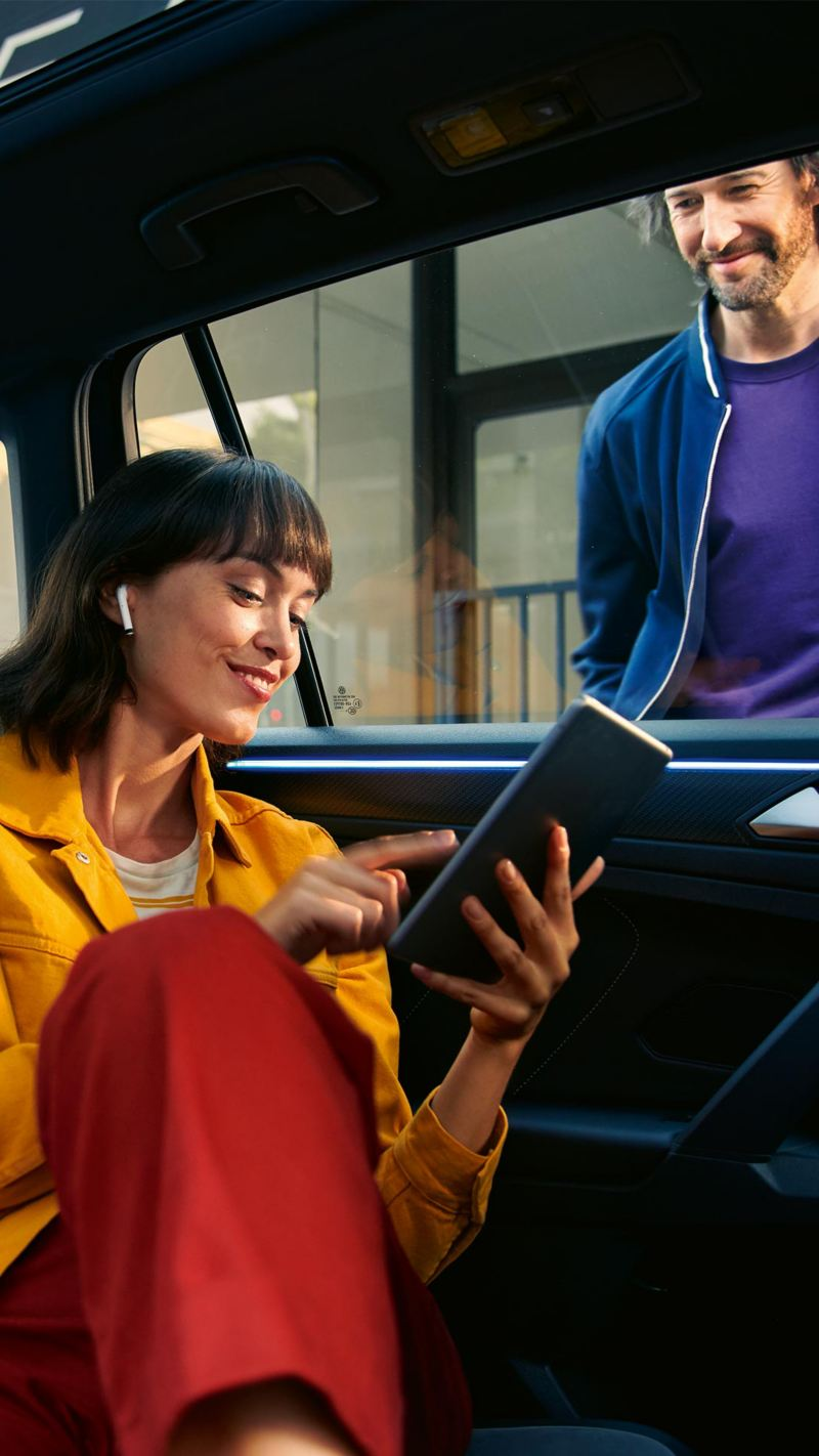 A woman using a tablet in the back seat of a car