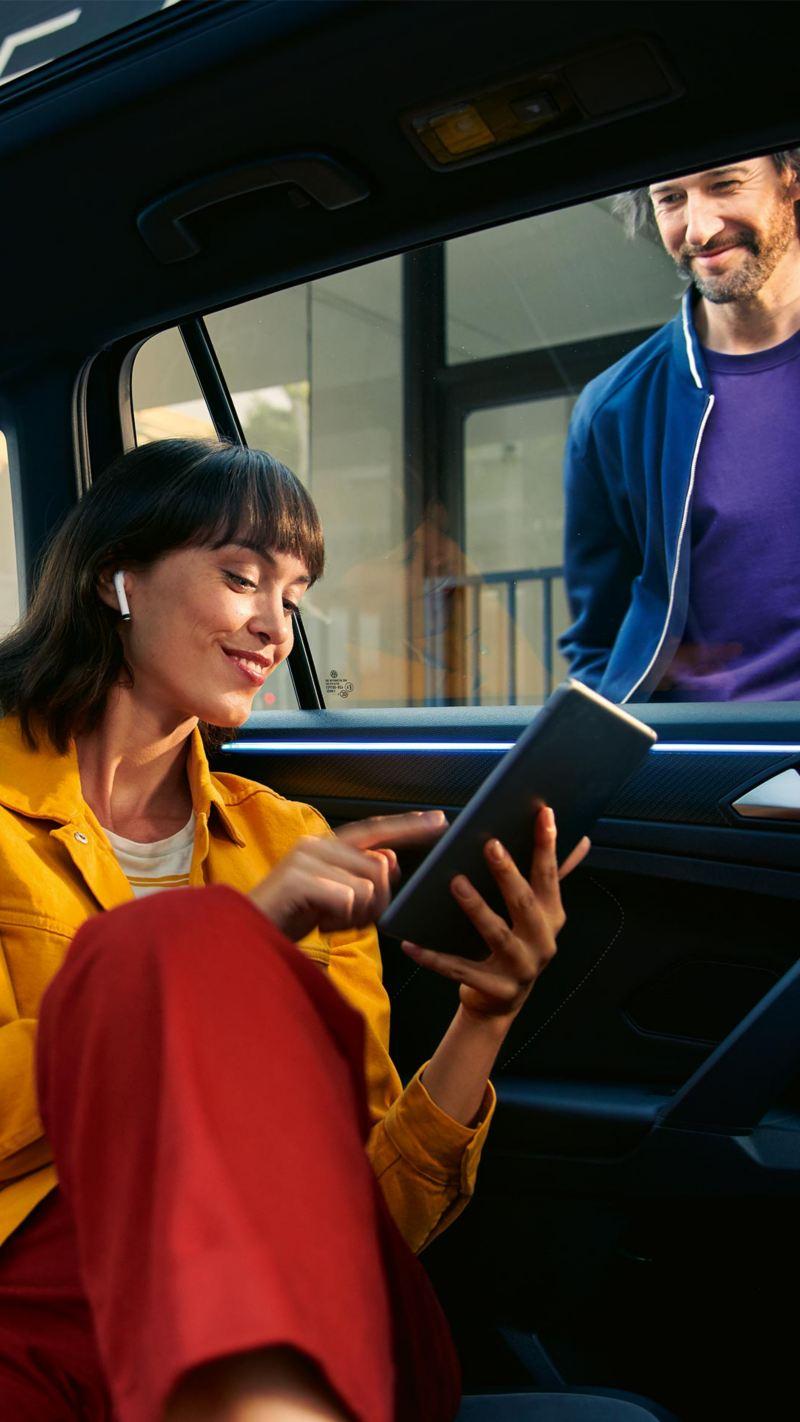 Uma senhora a utilizar um tablet no banco traseiro de um carro