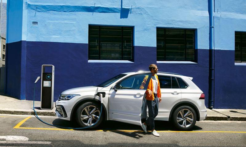 Nouveau Tiguan Hybride Rechargeable blanc en charge en ville devant mur bleu avec homme qui sort de la voiture