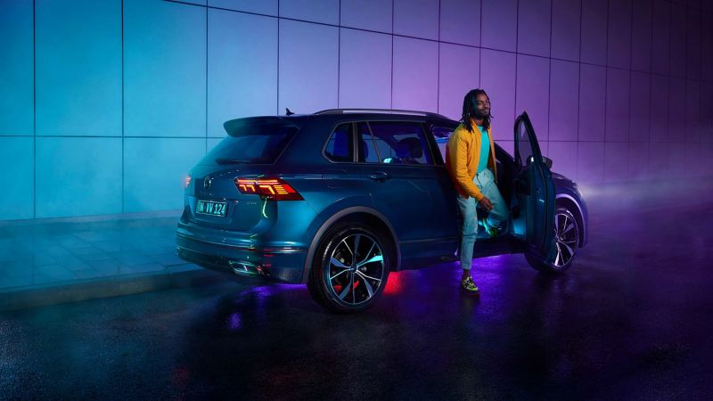 Person stepping out of driver side door of Volkswagen Tiguan.