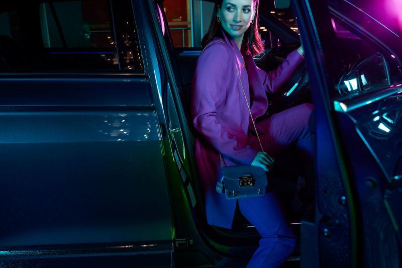 Woman sitting in drivers seat of Volkswagen Tiguan with door open.