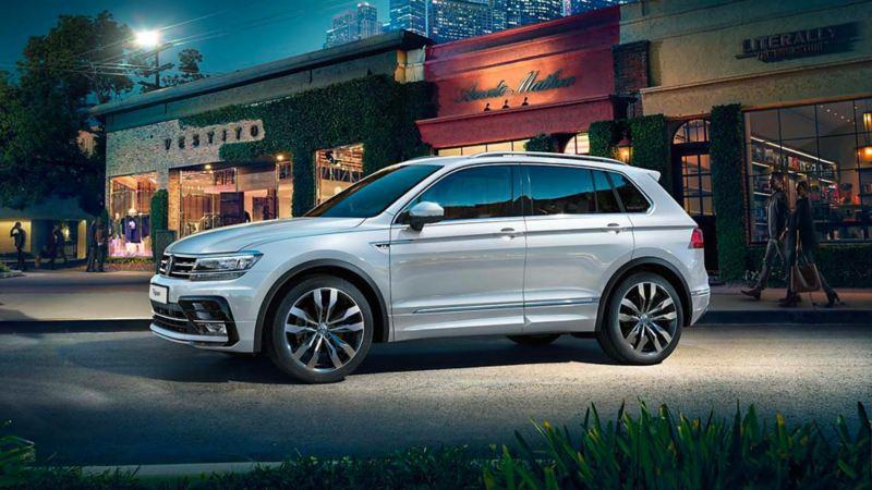 Vista laterale di Volkswagen Tiguan parcheggiata davanti ad un negozio.