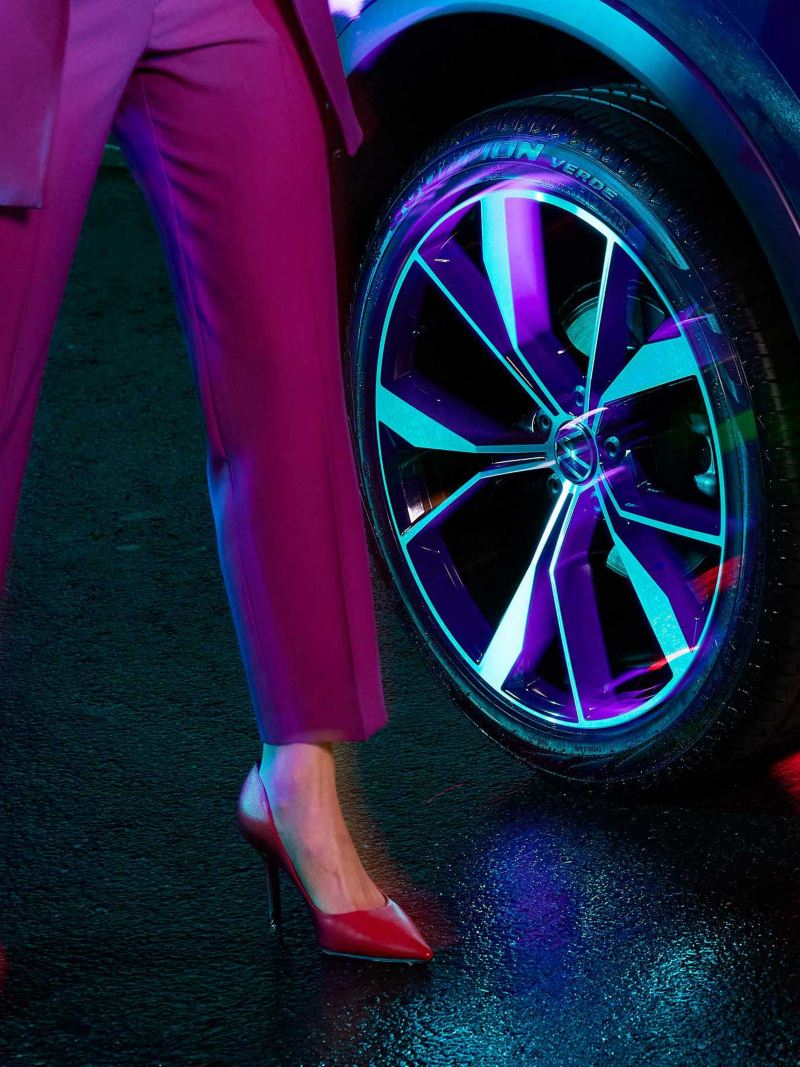 Close up of wheel of Volkswagen Tiguan with model standing next to it.