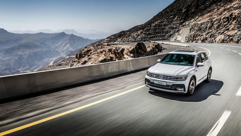 A white Volkswagen Tiguan driving around a mountain bend