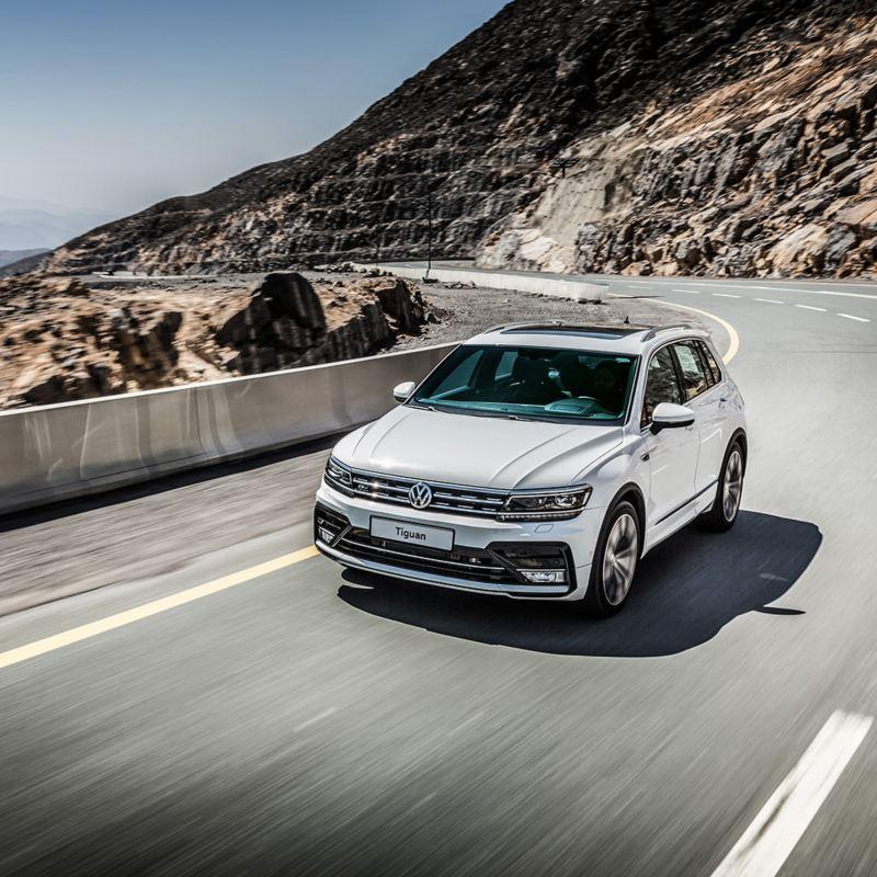 Volkswagen Tiguan driving around corner on a mountain