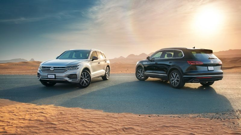 2 Volkswagen Touareg models parked next to each other on a desert road in the Middle East