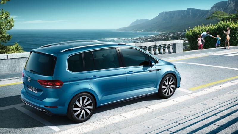 Seitenansicht eines blauen VW Touran, im Hintergrund ist das Meer zu sehen.