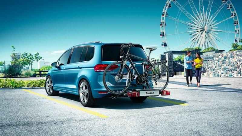 Vista 3/4 posteriore di Volkswagen Touran parcheggiata vicino a una ruota panoramica.