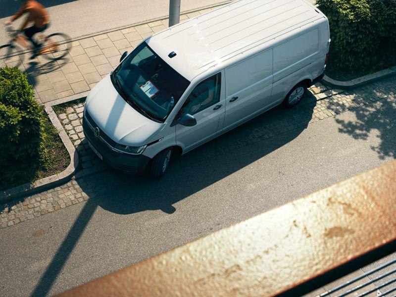 Bildet viser en hvit Volkswagen Transporter varebil sett ovenifra som står parkert i en parkeringslomme