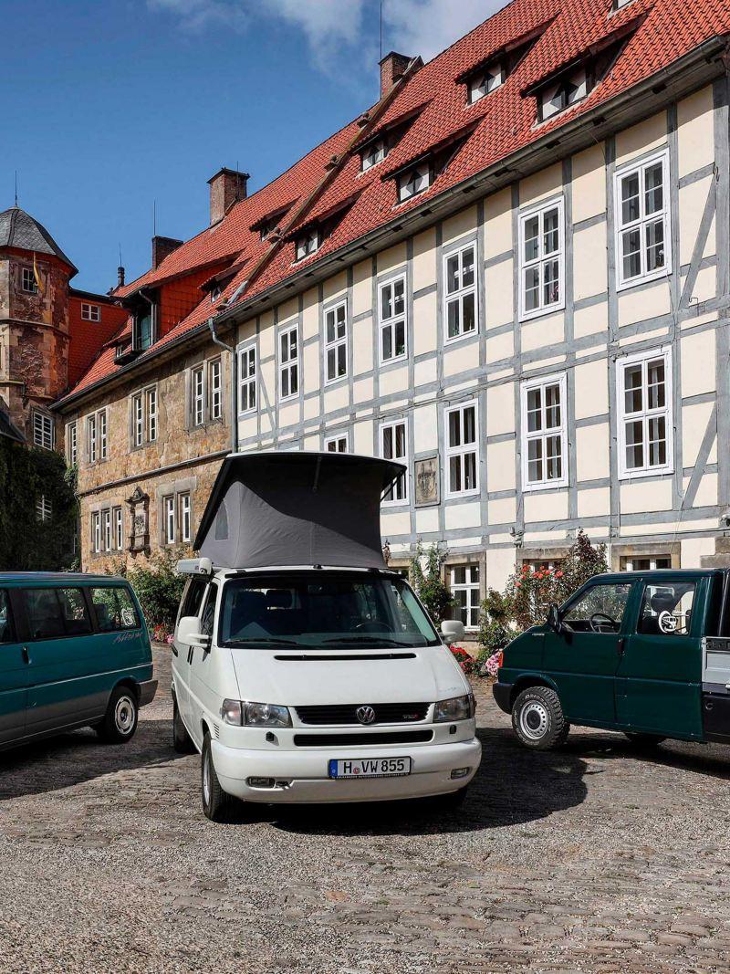 Três VW T4 em frente a uma casa típica na Alemanha.