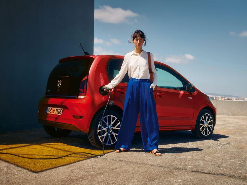 Nainen kiinnittää e-up! autoon latauspistoketta. Auto on kuvattu takaviistosta ja sijaitsee latauspisteen vieressä