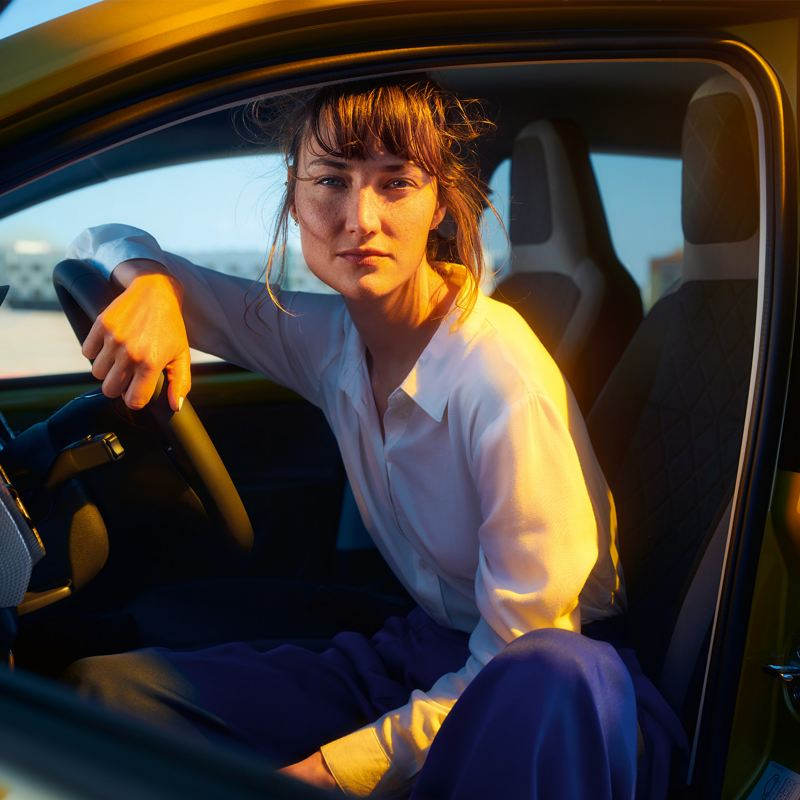Frau sitzt auf dem Fahrersitz eines VW e-up! Bei geöffneter Fahrertür und blickt in die Kamera.