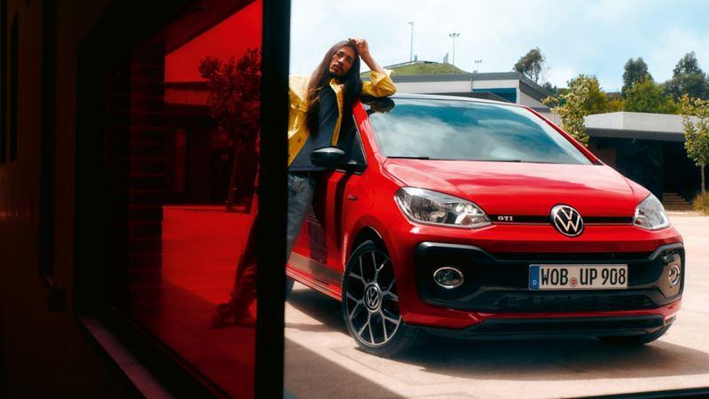 Mann mit langen Haaren lehnt an der Beifahrertür eines roten VW up! GTI auf einer großen Betonfläche vor einem modernen Gebäude.