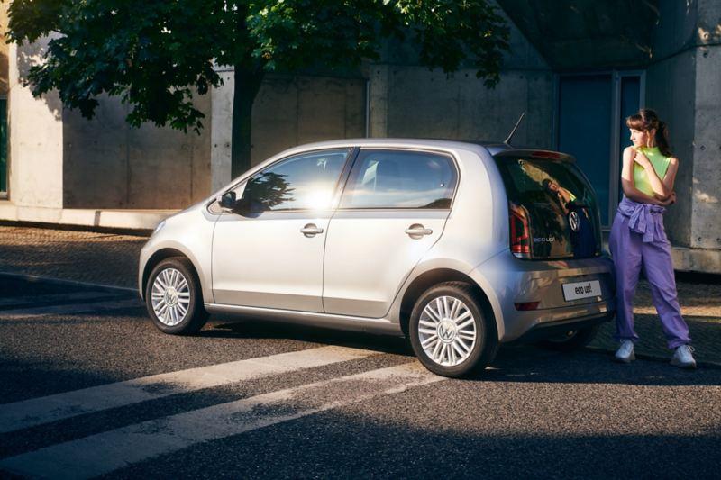 Una ragazza in piedi dietro a Volkswagen eco-up!, vista 3/4 posteriormente e parcheggiata a bordo di una strada cittadina.